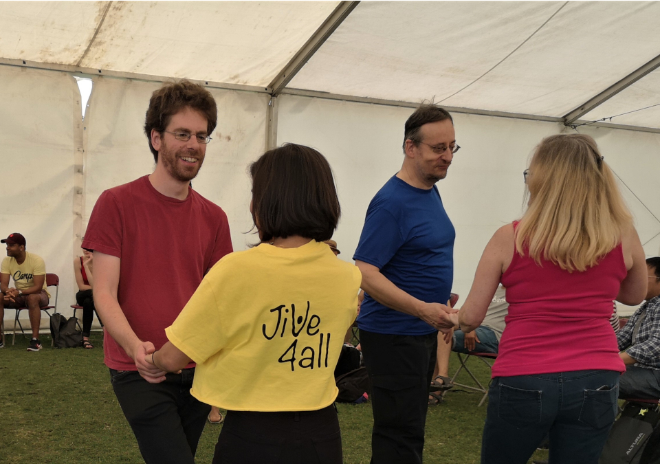 People dance together in a marquee, one is wearing a yellow Jive4All t-shirt