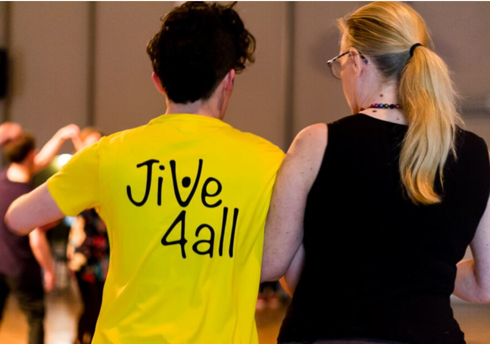 Two people with backs to camera dancing, one wearing Jive4All t-shirt