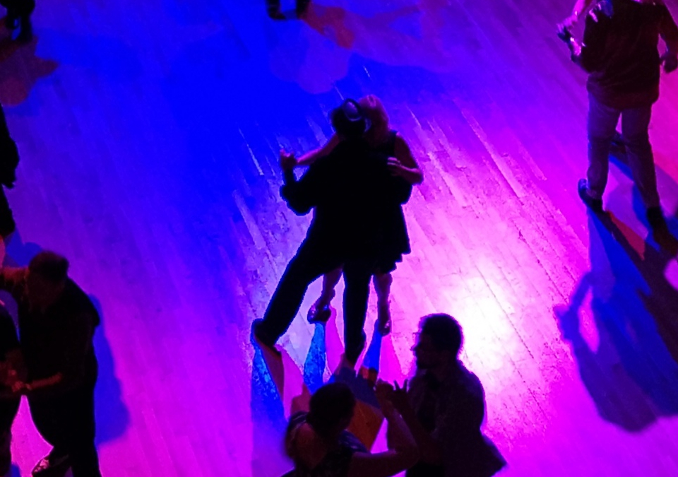 Two people dancing Tango-style, sihouetted.