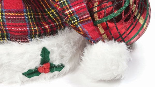 Image of a tartan Santa hat alongside a tartan Christmas tree bauble.